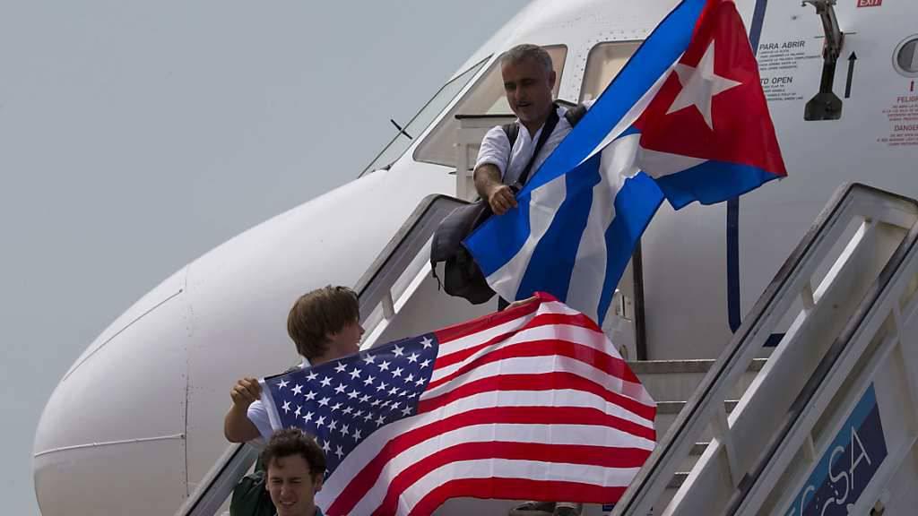 Zwei Passagiere entsteigen in Santa Clara der Maschine mit den Nationalflaggen beider Länder