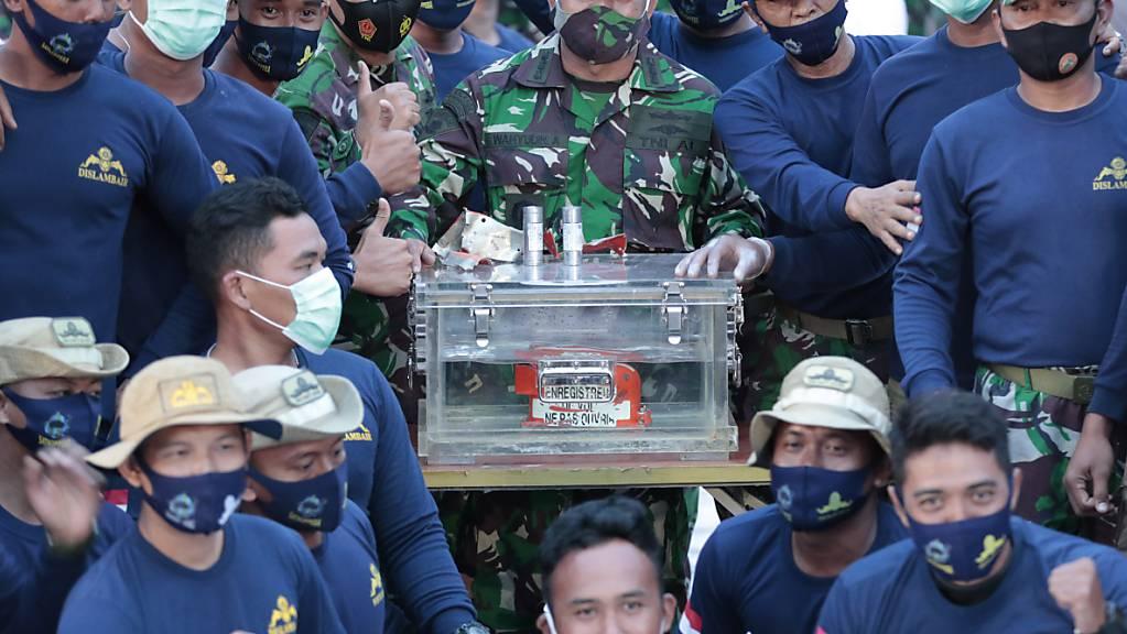 dpatopbilder - Personal der indonesischen Marine steht neben der Box mit dem Flugdatenschreiber des Sriwijaya Air Fluges SJ-182. Taucher haben nach tagelanger Suche auf dem Meeresgrund vor der Insel Java einen der Flugschreiber der verunglückten indonesischen Passagiermaschine geborgen. Foto: Dita Alangkara/AP/dpa