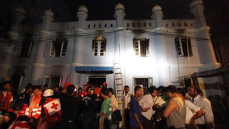 Viele Menschen versammeln sich vor der Moschee, wo in der Nacht auf den 2. April ein Feuer 13 Menschenleben forderte.