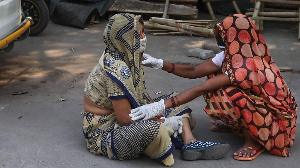 Die Angehörige eines Covid-19-Opfers wird während der Einäscherung des Leichnams im Krematorium Nigambodh Ghat in Neu-Delhi getröstet.