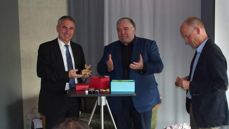 Walter Tschudin übergibt den Referenten Regierungsrat Alex Hürzeler (links) und Kulturchef Thomas Pauli je ein Replikat einer römischen Öllampe aus Vindonissa