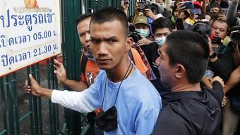 Panupong Jadnok, Pro-Demokratie-Aktivist, will im Rahmen der Demonstrationen ein Tor der Thammasat-Universität öffnen. Foto: Sakchai Lalit/AP/dpa