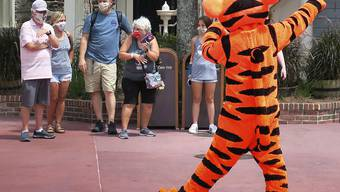 Willkommen mit Schutzmaske: Tigger begrüsst Gäste beu der Wiedereröffnung des Magic Kingdom in Walt Disney World in Lake Buena Vista, Florida.