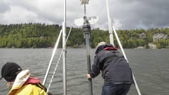 Forschende der Eawag bei der Entnahme eines Sedimentbohrkerns aus dem Lac de Joux.