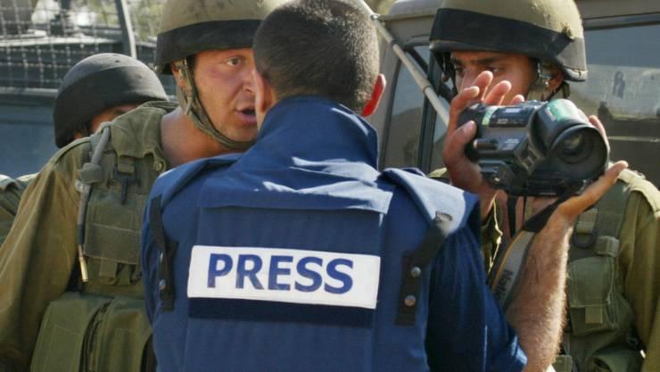 Ein israelischer Soldat bedeckt die Kamera eines Journalisten. Die Zahl der als sicher geltenden Länder, in denen Journalisten uneingeschränkt arbeiten können, nimmt weiter ab. Auf der Rangliste der Pressefreiheit von Reporter ohne Grenze liegt die Schweiz auf Rang 6. (Symbolbild)