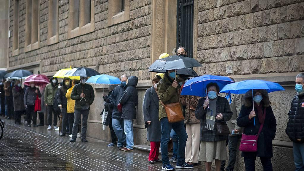Menschen stellen sich vor einem Wahllokal an, bevor sie ihre Stimme für die katalanischen Regionalwahlen abgeben. Foto: Emilio Morenatti/AP/dpa