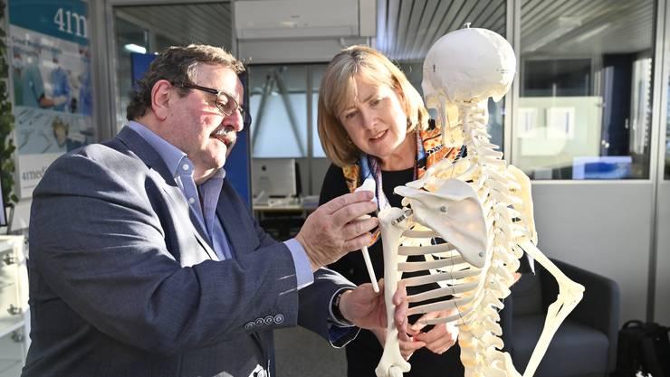 Inhaber Robert Frigg zeigt der Botschafterin ein neu entwickeltes Implantat für ein Schultergelenk, das nicht verschraubt werden muss.