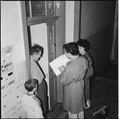 Eine Zählerin und ein Zähler überreichen den Fragebogen der Volkszählung 1960 persönlich an der Wohnungstüre.