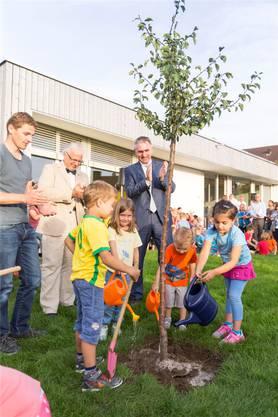 Regierungsrat Alex Hürzeler (rechts) und Gemeindeammann Jürg Link (Mitte) feuern die Kinder beim Baumpflanzet an.