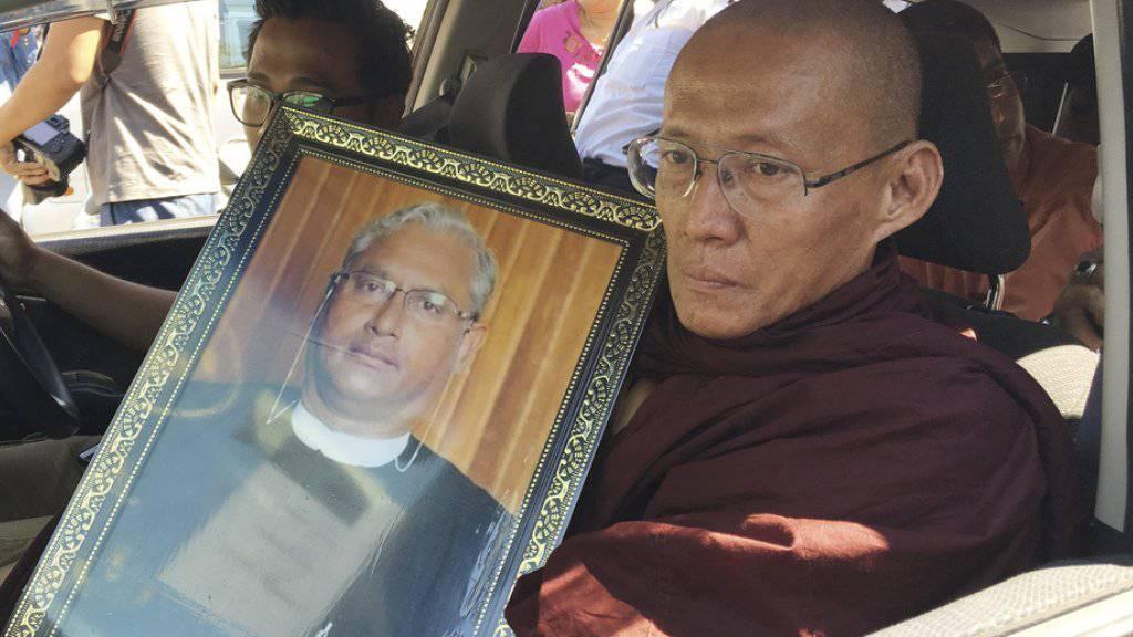 Ein buddhistischer Mönch am Montag in Yangon mit einem Bild des Ermordeten.