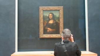Ein Besucher des Louvre fotografiert die «Mona Lisa» von Leonardo da Vinci. Foto: Sabine Glaubitz/dpa