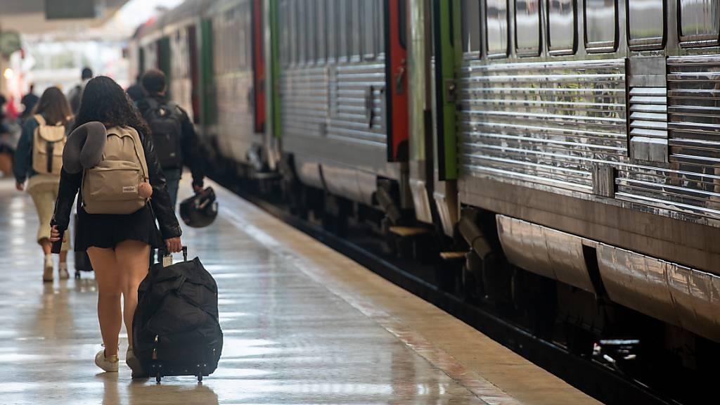 Menschen gehen im Bahnhof Santa Apolonia im Zentrum der portugiesischen Hauptstadt über einen Bahnsteig. Foto: Paulo Mumia/dpa
