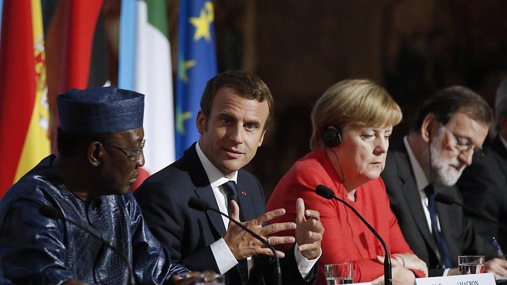 In Paris an einem Tisch: Der französische Präsident und Gastgeber Emmanuel Macron (Mitte), flankiert (links) vom Präsidenten Tschads, Idriss Déby, und rechts von der deutschen Kanzlerin Angela Merkel sowie dem spanischen Regierungschef Mariano Rajoy.