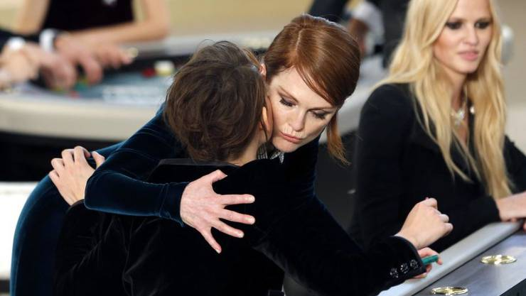 Julianne Moore (m) umarmt an einem Roulette-Tisch Kristen Stewart (l), dahinter das britische Model Lara Stone