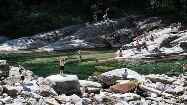 Menschen geniessen sonniges Wetter am Verzascafluss im Verzascatal in Lavertezzo.