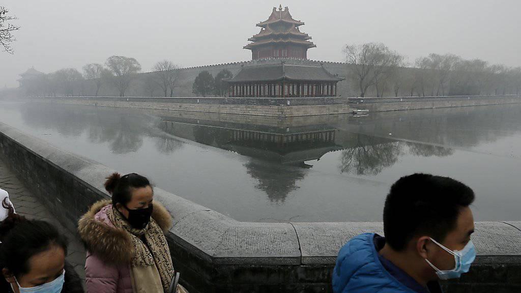 Maskierte Menschen bei der Verbotenen Stadt in Peking: Nach drei Tagen hat die Stadt die höchste Smog-Warnstufe aufgehoben. (Archivbild)