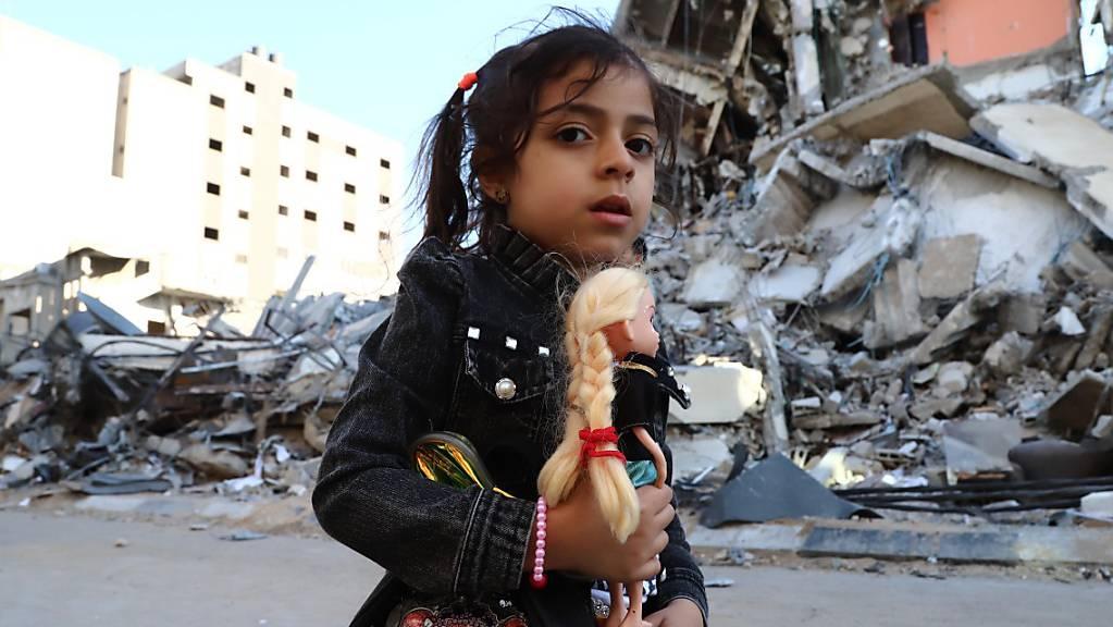 Ein Mädchen geht vorbei an von Luftangriffen zerstörten Häusern. Seit dem 10. Mai beschiessen militante Palästinenser Israel mit Raketen. Israels Armee reagiert darauf mit Angriffen auf Ziele im Gazastreifen, vor allem durch die Luftwaffe. Auf beiden Seiten gab es Tote.