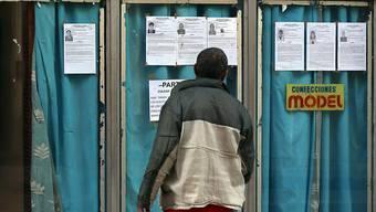 Mann liest die Beschreibungen der auf Kuba zur Wahl stehenden Personen.