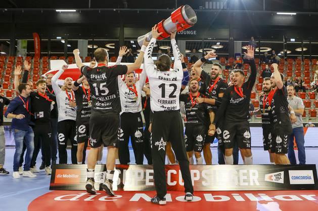 Die beiden Co-Captains Dario Ferrante (r.) und Tim Aufdenblatten (l.) präsentieren der Mannschaft die Supercup-Trophäe.