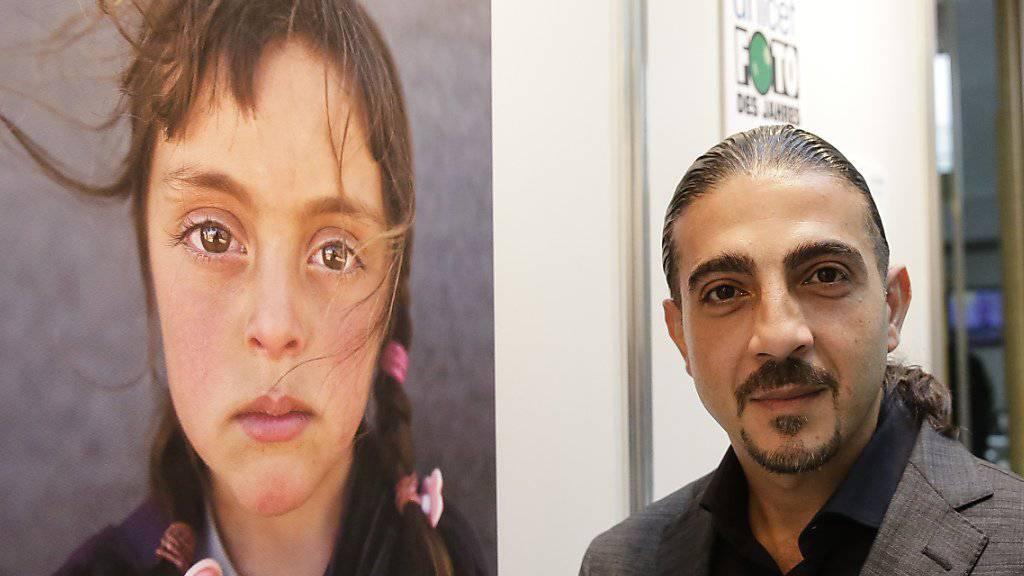Fotograf Muhammend Muheisen neben seinem Bild, das zum Unicef-«Foto des Jahres» gekürt wurde.