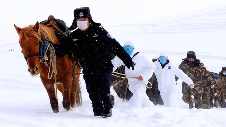 Chinesische Grenzsoldaten versuchen abgelegene Bergdörfer in China über das neuartige Coronavirus zu informieren. (Foto: A RAN/EPA Keystone-SDA)