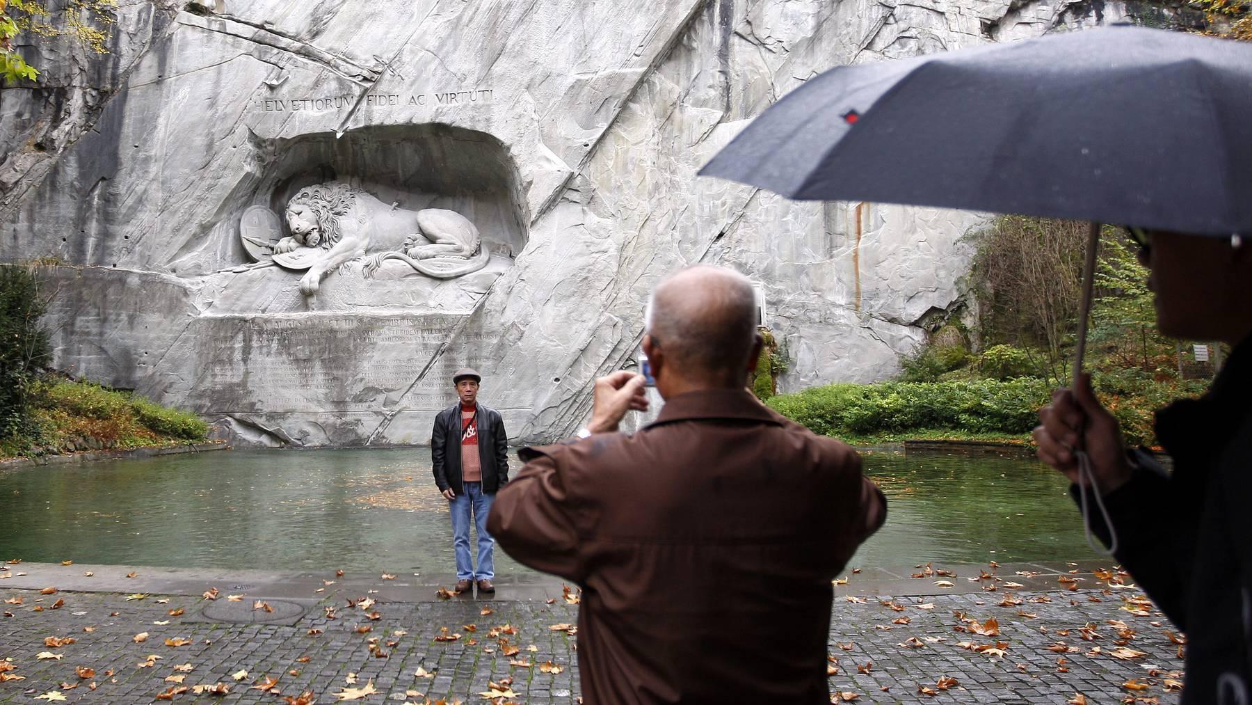 Chinesische Touristen besuchen am Mittwoch, 22. Oktober 2008 bei regnerischem Herbstwetter das Loewendenkmal in Luzern.