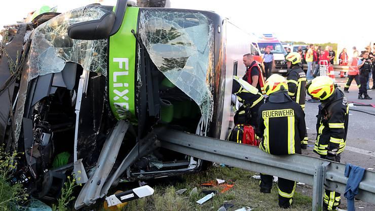 Einsatzkräfte der Feuerwehr stehen an der Unfallstelle neben dem verunglückten Bus in der Nähe von Leipzig.