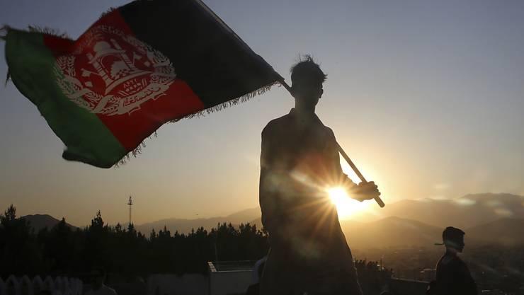 dpatopbilder - ARCHIV - Ein Mann schwenkt eine afghanische Nationalflagge. Foto: Rafiq Maqbool/AP/dpa