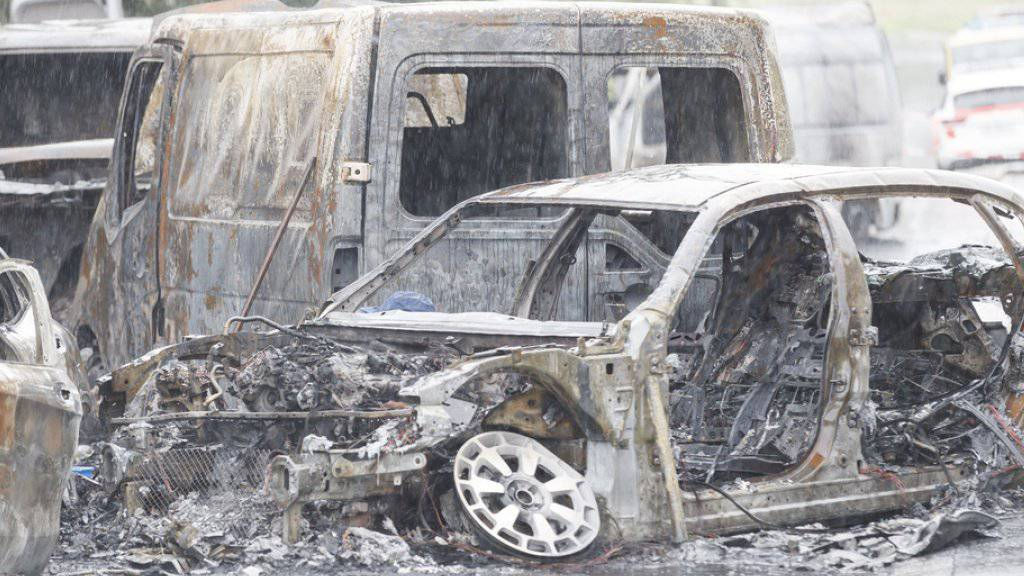 Die Wracks von mehreren ausgebrannten Fahrzeugen am Tatort in Mont-sur-Lausanne.