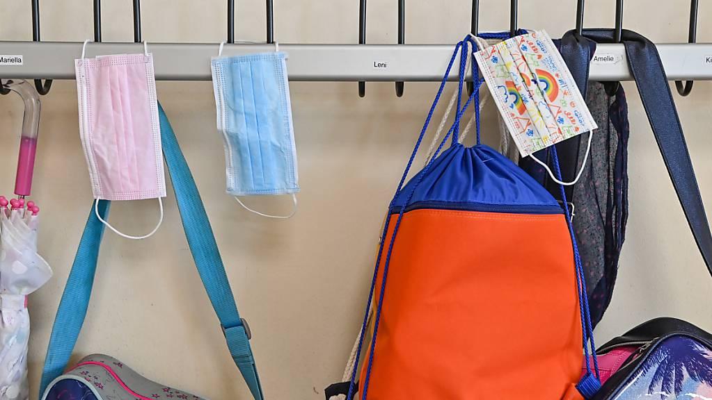 ARCHIV - Masken hängen an Kleiderhaken in einer Grundschule. Foto: Patrick Pleul/dpa-Zentralbild/ZB