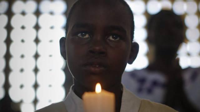 Kenianischer Bub hält eine Kerze während eines Gebets für die Opfer