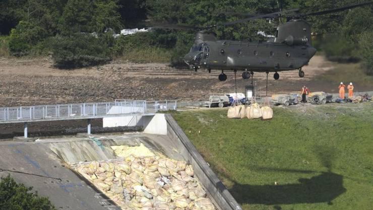 Die britische Air Force brachte mit Helikoptern Sandsätze zum gefährdeten Damm. (Archivbild)