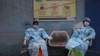Medizinische Mitarbeiterinnen in Schutzausrüstung ruhen sich vor der Entnahme von Speichelproben für Covid-19-Tests aus. Foto: Mahesh Kumar A/AP/dpa