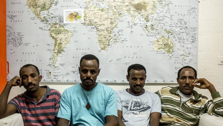 Vier Asylbewerber vor einer Weltkarte. «Dies war ein Fotoauftrag, der beeindruckende und interessante Begegnungen mit Menschen im Durchgangsheim Biberist ermöglichte.»