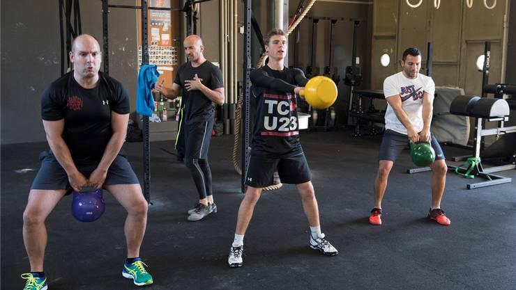 az-Volontär Lucius Müller (mit der gelben «Cattle Bell») legt sich ins Zeug.Im Hintergrund gibt CrossFit-Trainer Fabio Marchesan weitere Inputs. Alex Spichale