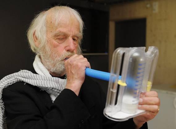 Pfarrer Sieber demonstriert ein Atemuebungsgerät, welches er nach seinem Autounfall zur Stärkung seiner Lunge hin und wieder einsetzen muss