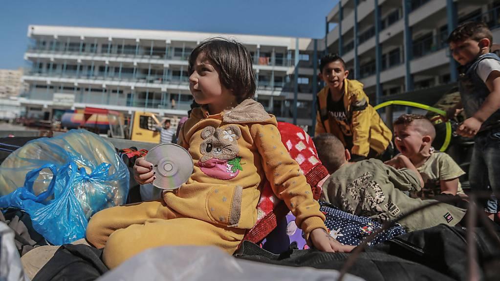 Palästinenser sitzen mit ihren Habseligkeiten vor einer UN-Schule, in der sie Schutz suchen. Sie mussten während der israelischen Luftangriffe aus ihren Häusern fliehen inmitten des eskalierenden Aufflammens der israelisch-palästinensischen Gewalt.