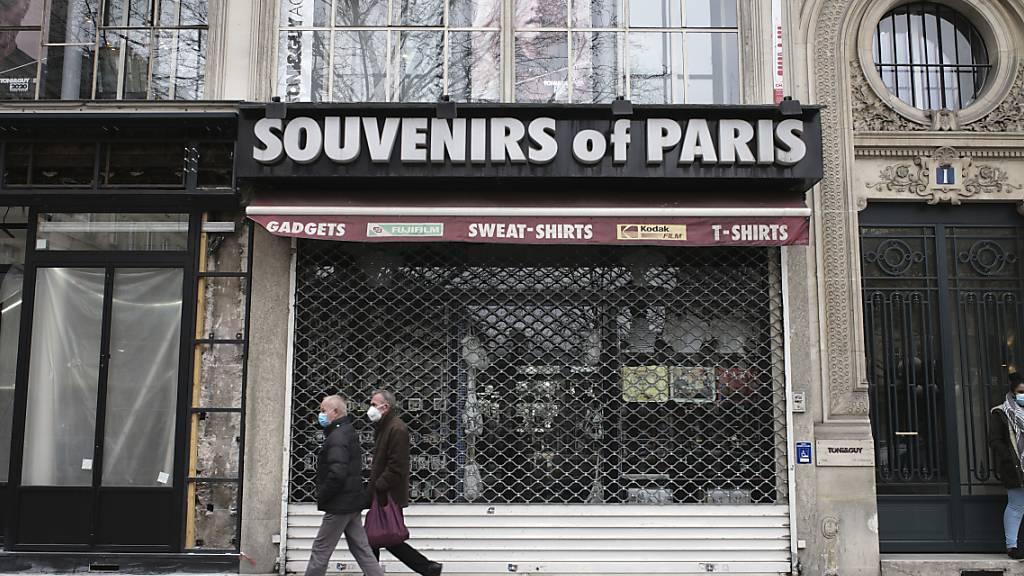 Passanten gehen an einem geschlossenen Souvenirgeschäft vorbei. Foto: Lewis Joly/AP/dpa