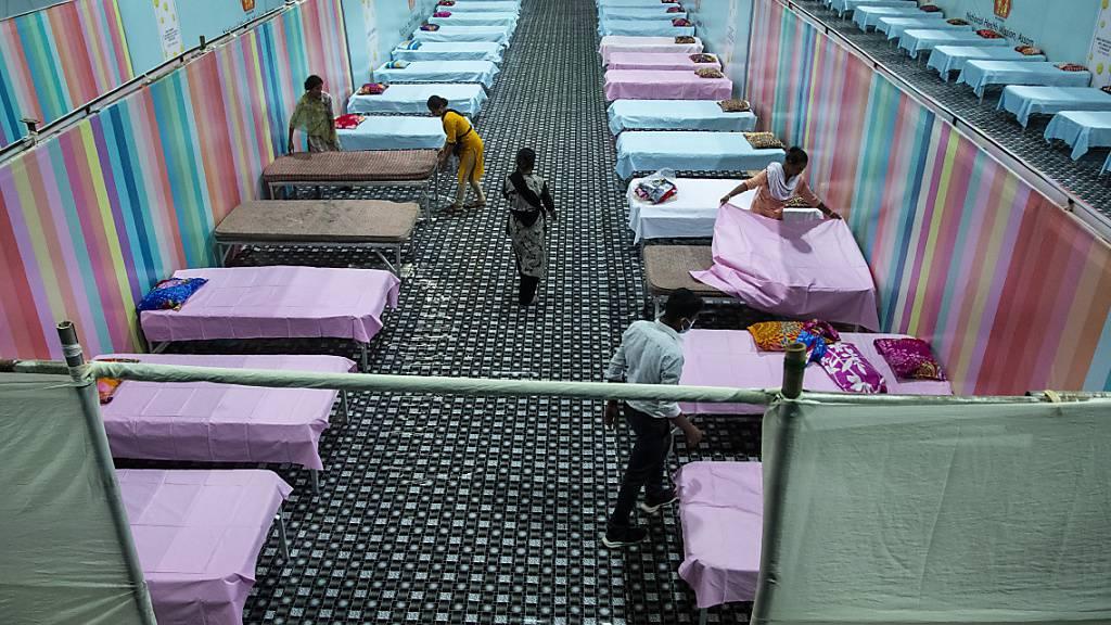 dpatopbilder - Arbeiter stellen provisorische Betten für Corona-Patienten in einer Stadionhalle auf. Foto: Anupam Nath/AP/dpa