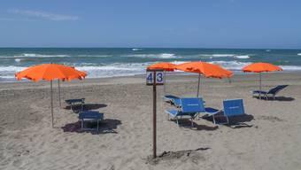 Werden hier bald Sonnenhungrige aus der Schweiz liegen? Liegestühle und Sonnenschirme am Strand von Capocotta in der Nähe von Rom.