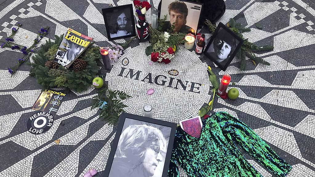 ARCHIV - Fotos, Blumen und Kerzen stehen auf der Gedenkstätte Strawberry Fields im Central Park zur Erinnerung an John Lennon. Vor 50 Jahren veröffentlichte John Lennon seinen Song «Imagine». Das Lied gilt bis heute als hoffnungsvolle Hymne für den Weltfrieden, obwohl einige Zeilen immer wieder zu Diskussionen anregen. (zu dpa «Ewige Friedenhymne des Träumers: John Lennons «Imagine» wird 50») Foto: Mark Lennihan/AP/dpa