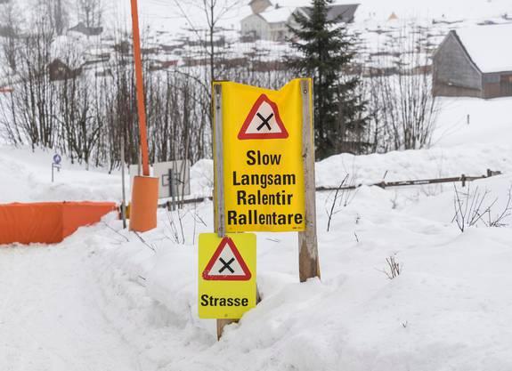 Tafeln warnen Schlitler in Jakobsbad, dass hier eine Strasse die Piste quert.
