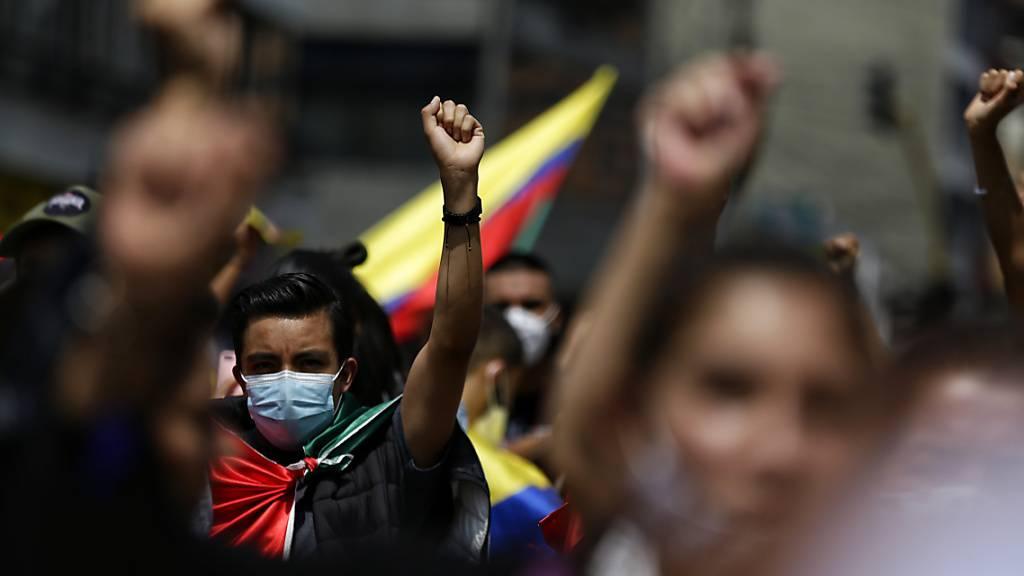 Demonstranten mit Mund-Nasen-Bedeckung ballen die Faust während einer Kundgebung am siebten Tag der Proteste gegen die Regierung inmitten der Corona-Pandemie. Nach tagelangen Protesten gelten mehr als 370 Menschen als vermisst. Foto: Sergio Acero/colprensa/dpa