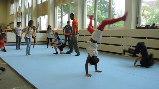 Zeitvertreib in der Turnhalle: Ein Zivilschützer versucht, den Kindern Capoeira beizubringen.
