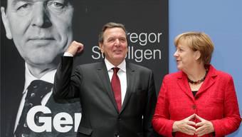 Gute Stimmung: Gerhard Schröder wird bei der Präsentation seiner Biografie von Bundeskanzlerin Angela Merkel unterstützt. Michael Sohn/AP/Keystone