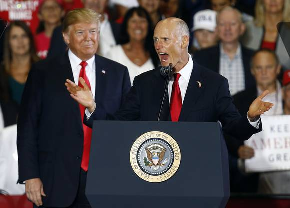 Der republikanisch Kandidat Rick Scott bei einer Rede am 3. November, hinten links sein bester Wahlkampfhelfer.