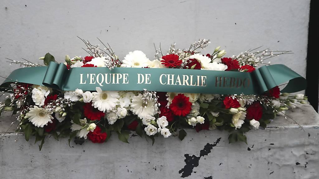 Ein Blumenkranz mit der Aufschrift «Das Team von Charlie Hebdo» liegt vor dem ehemaligen Bürogebäude des Satiremagazins. Foto: Michel Euler/POOL AP/AP/dpa