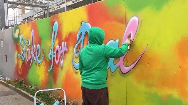 Graffiti-Künstler Raphael Fahrni verschönert die Stapferhaus-Baustelle.