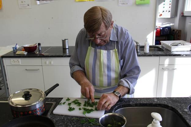 Reinhard Lüscher hackt Petersilien für die Tomatensuppe