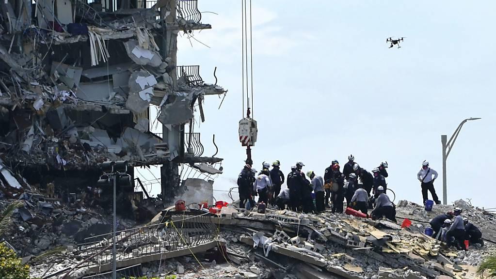 dpatopbilder - Such- und Rettungskräfte suchen nach Überlebenden in den Trümmern im dem teilweise eingestürzten zwölfstöckigen Gebäude in Surfside in Florida. Foto: Lynne Sladky/AP/dpa